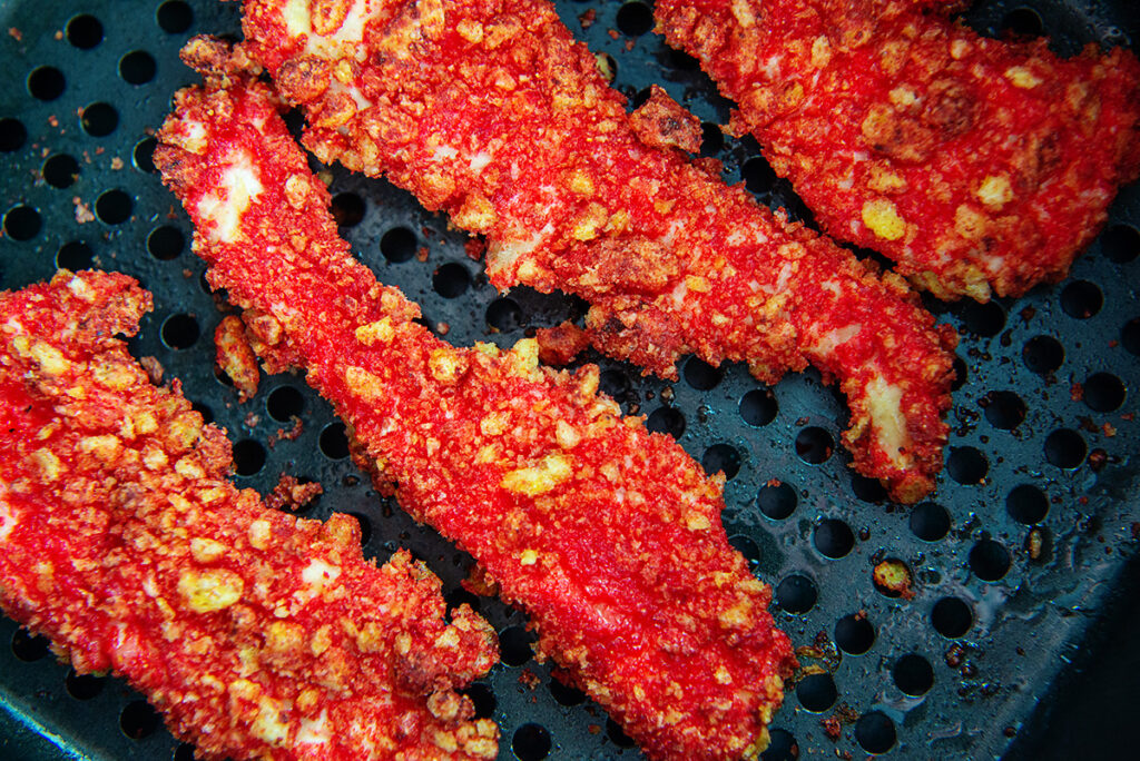 Close up of chicken strips coated in cheetos cooking in an air fryer basket