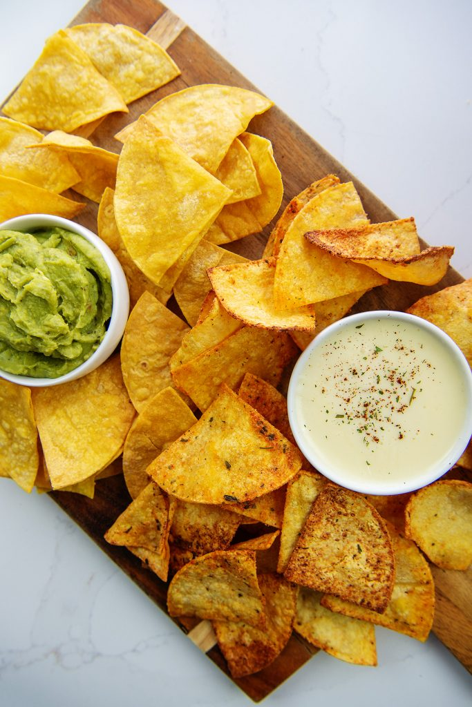Cutting board with chips, guacamole, and queso dip