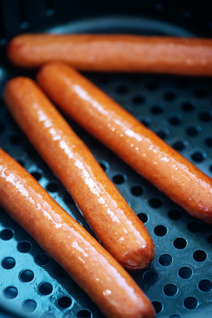hot dogs cooking in an air fryer basket