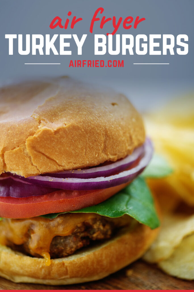 Close up of a turkey cheeseburger with onion, tomato, and lettuce on it.