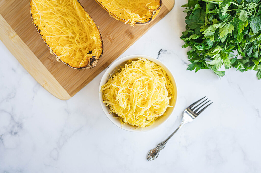 Overhead view of a spaghetti squash split open next to a bowl of cooked squash