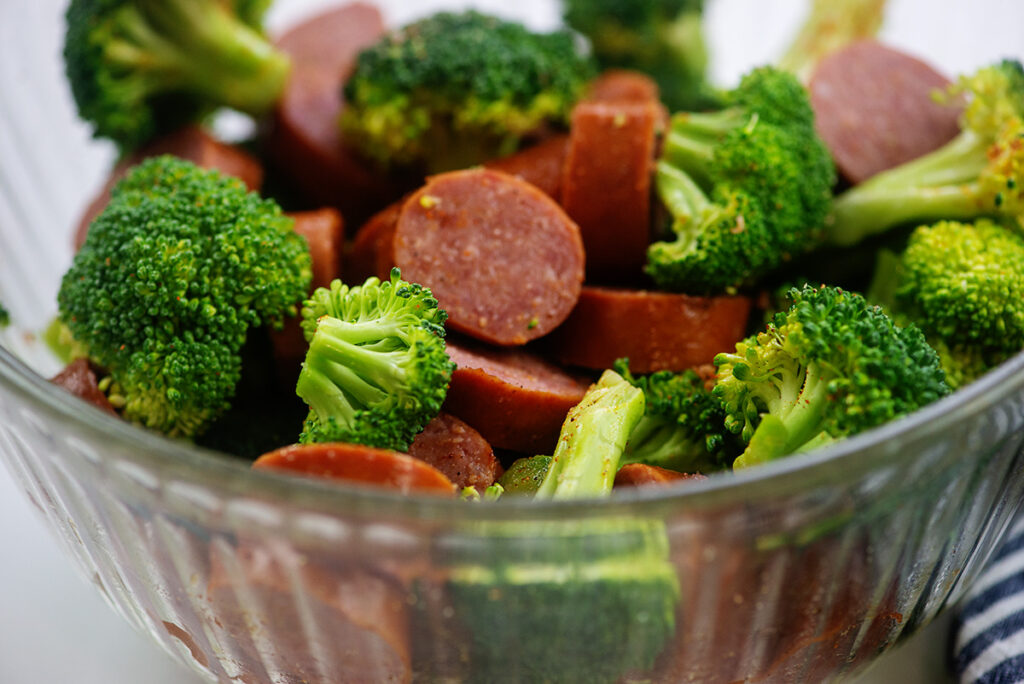 close up of broccoli and cut sausage in a clear glass bowl