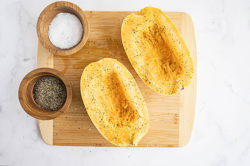 salt and pepper on a cutting board next to a split open spaghetti squash