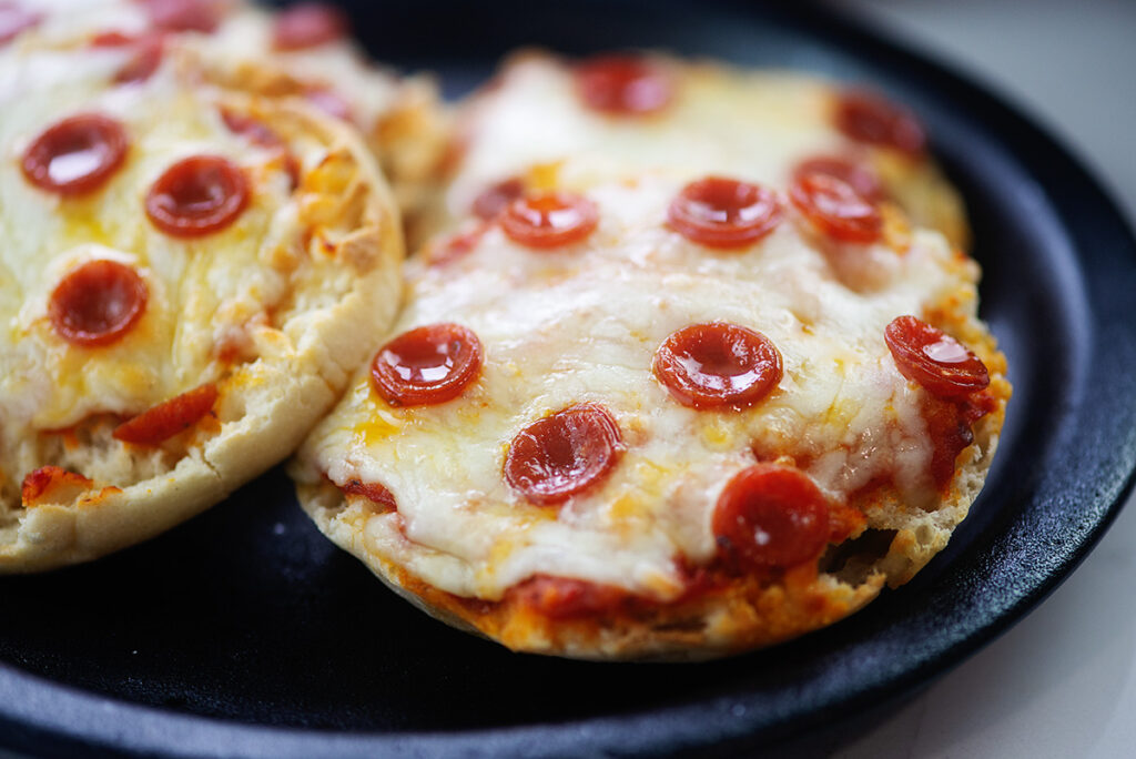 Two english muffin pizzas on a black plate