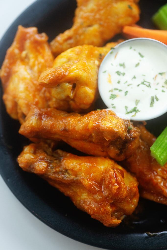 ranch dressing and chicken wings on a small black plate