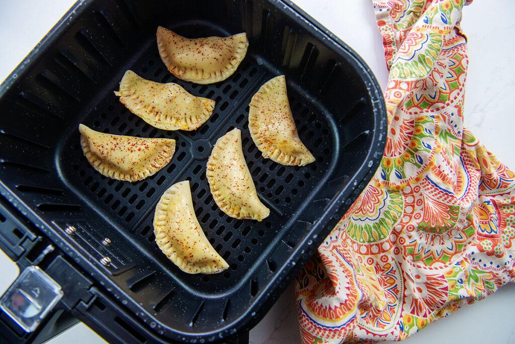 Seasoned empanadas cooking in an air fryer