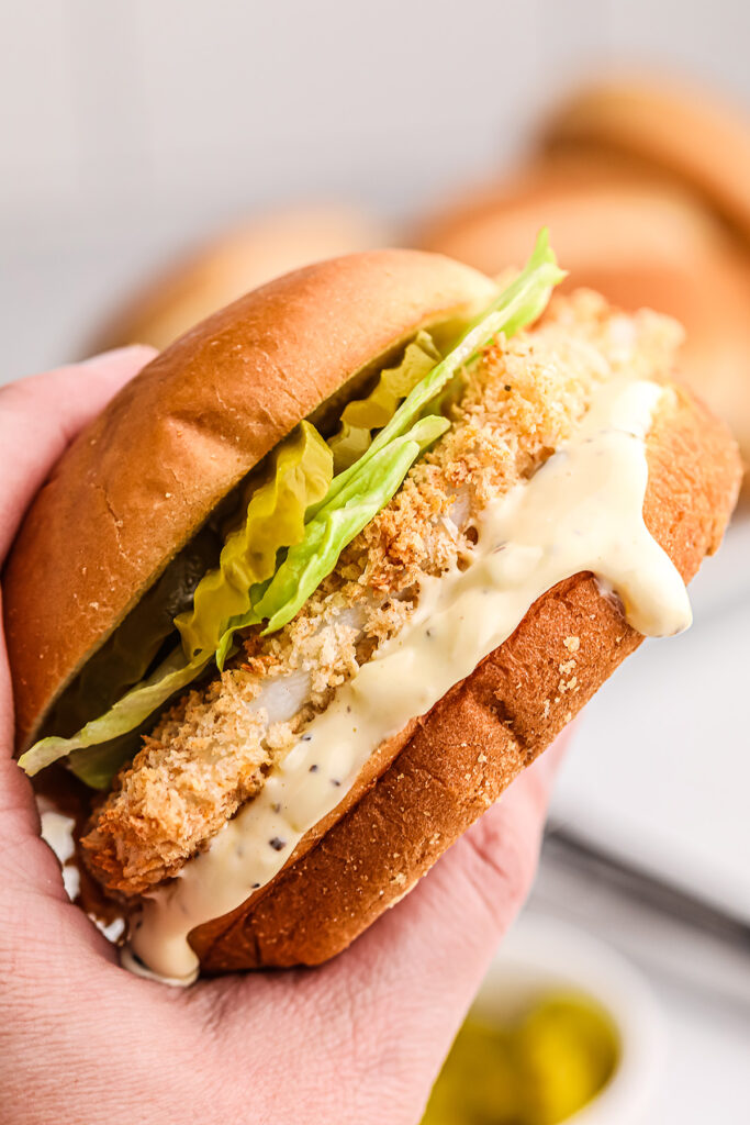 a person holding up a fish sandwich with tartar sauce