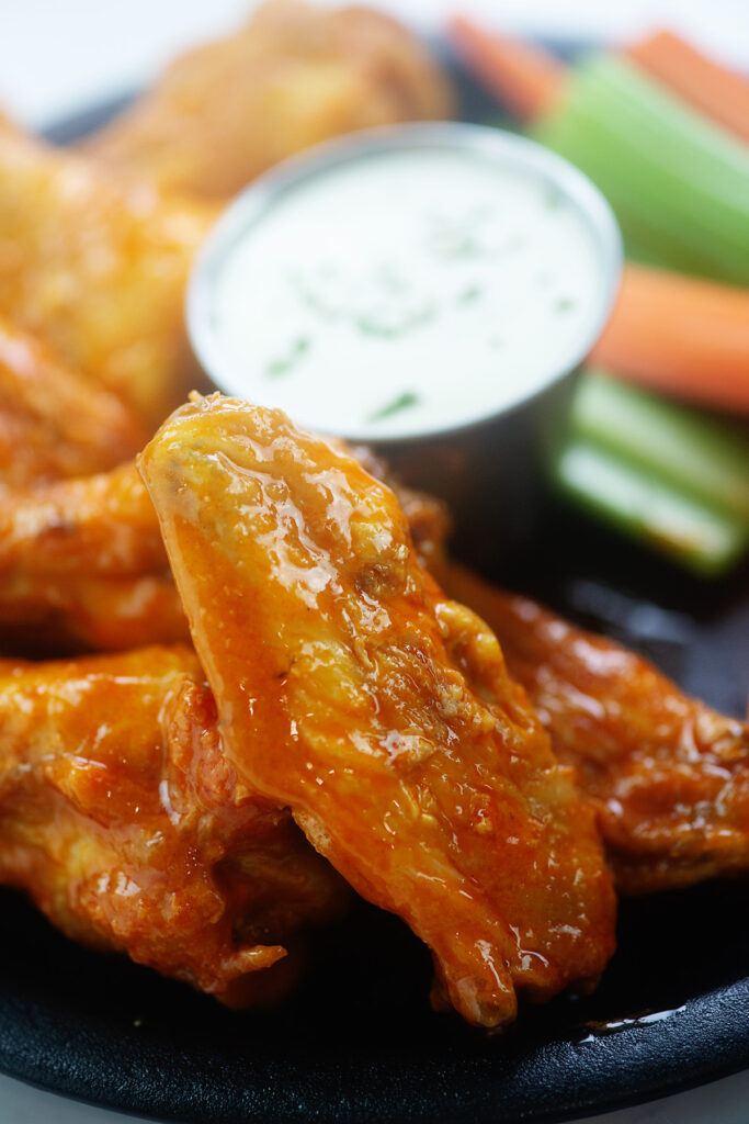 a chicken wing leaned up against another wing on a plate with ranch dressing
