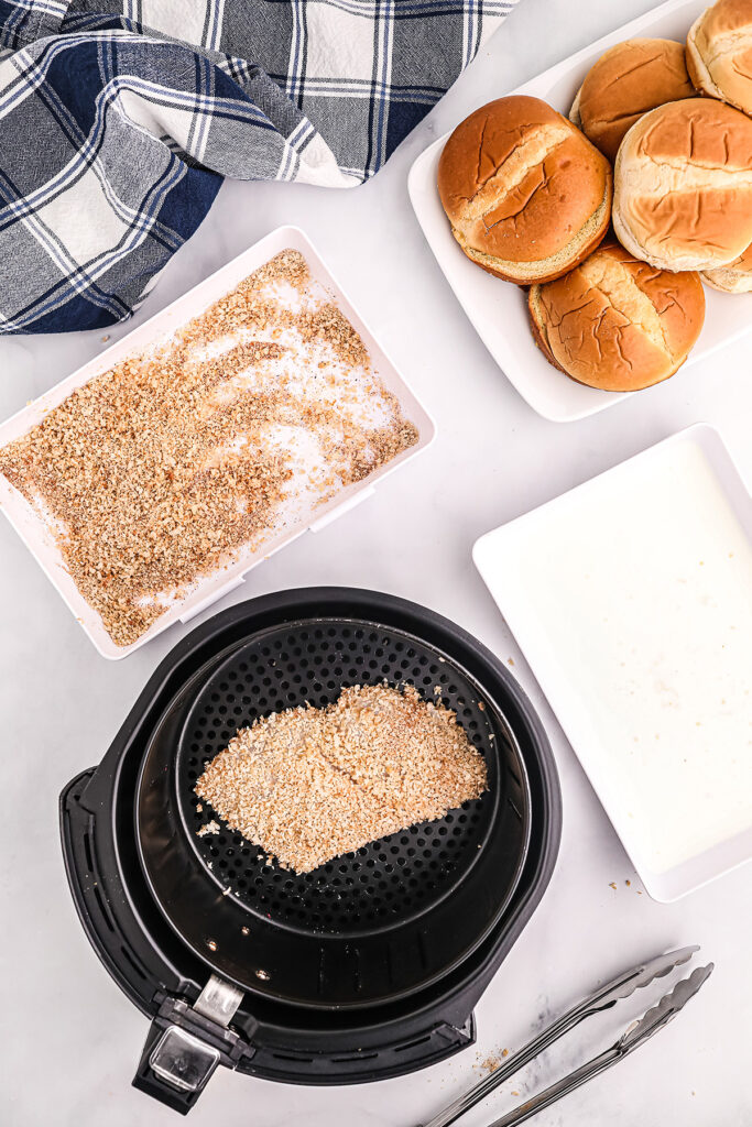 breaded fish filet in an air fryer basket next to buns