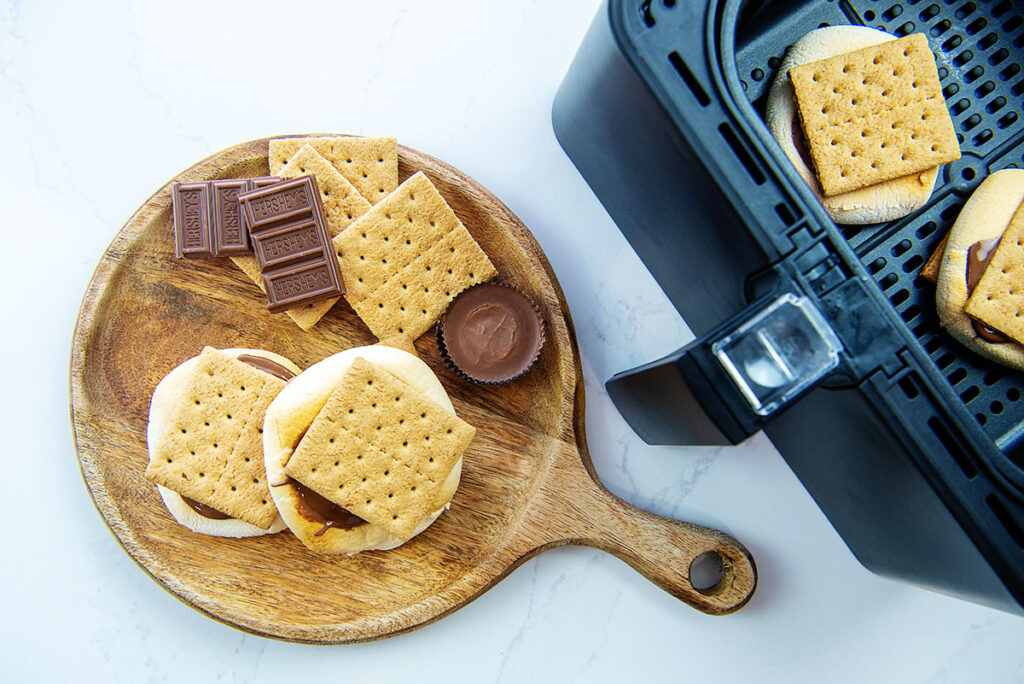smores on a wooden plate next to an air fryer