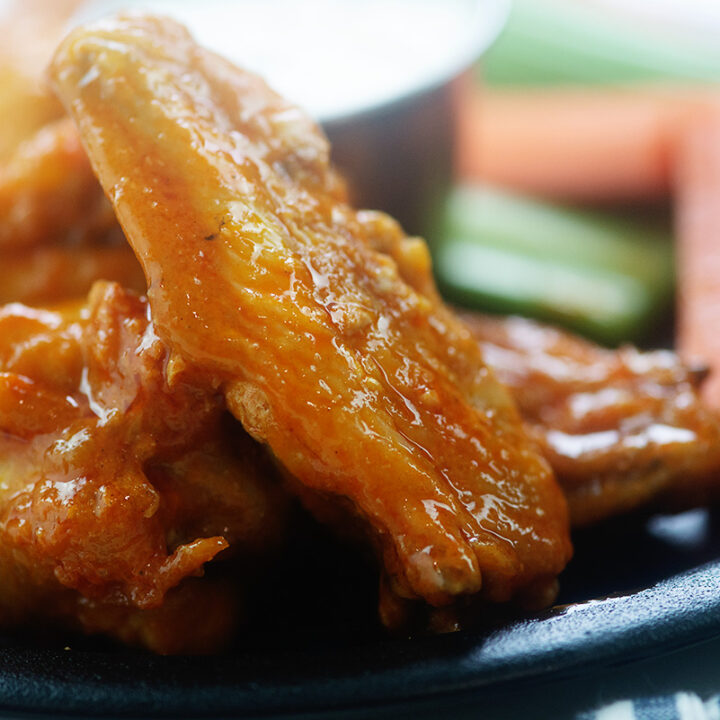 Close up of buffalo chicken wings stacked up