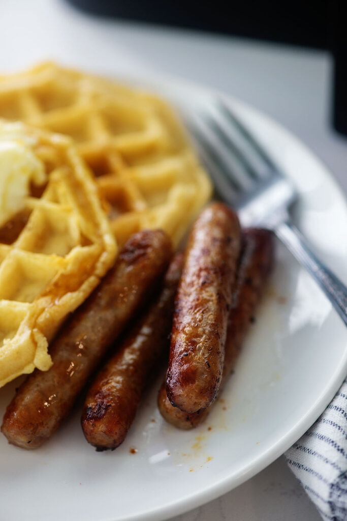 Sausage links and waffles on a small white plate.