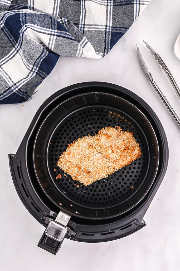 a breaded fish fillet in an air fryer basket