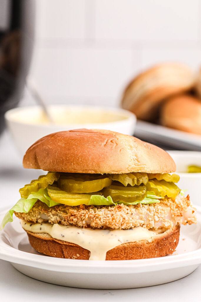 A close up of a fish sandwich in front of a bowl of tartar sauce