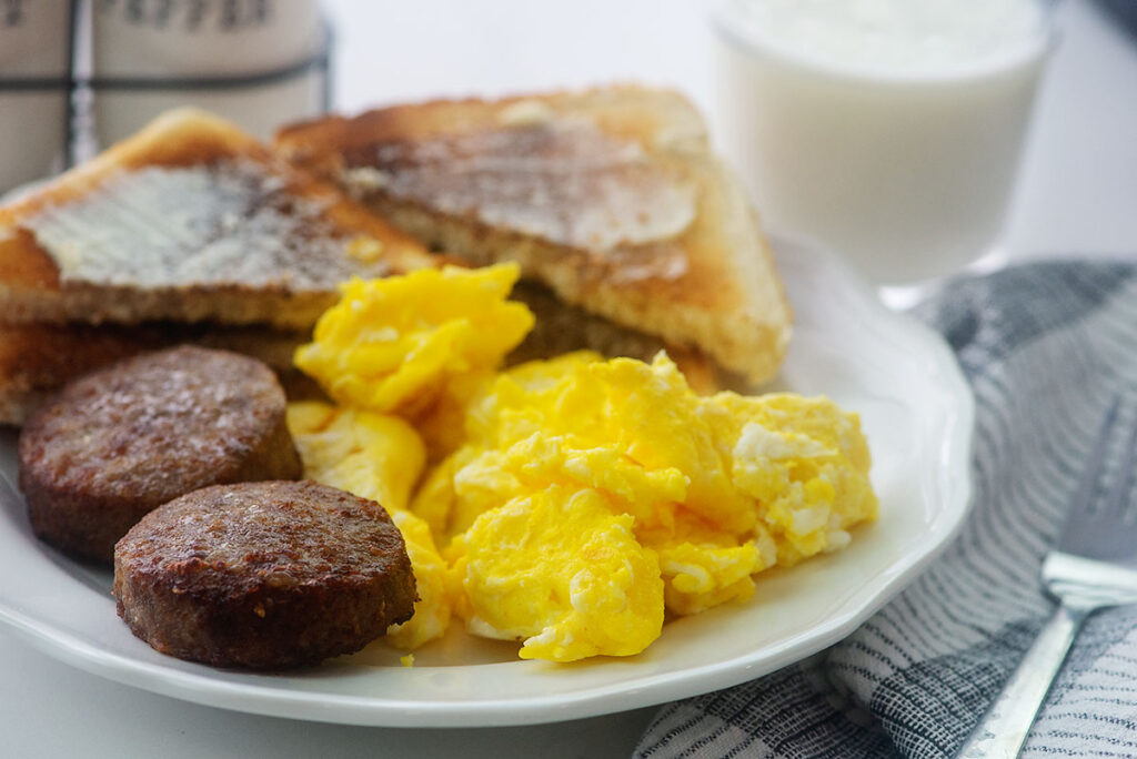 Sausage patties on a white plate with scrambled eggs