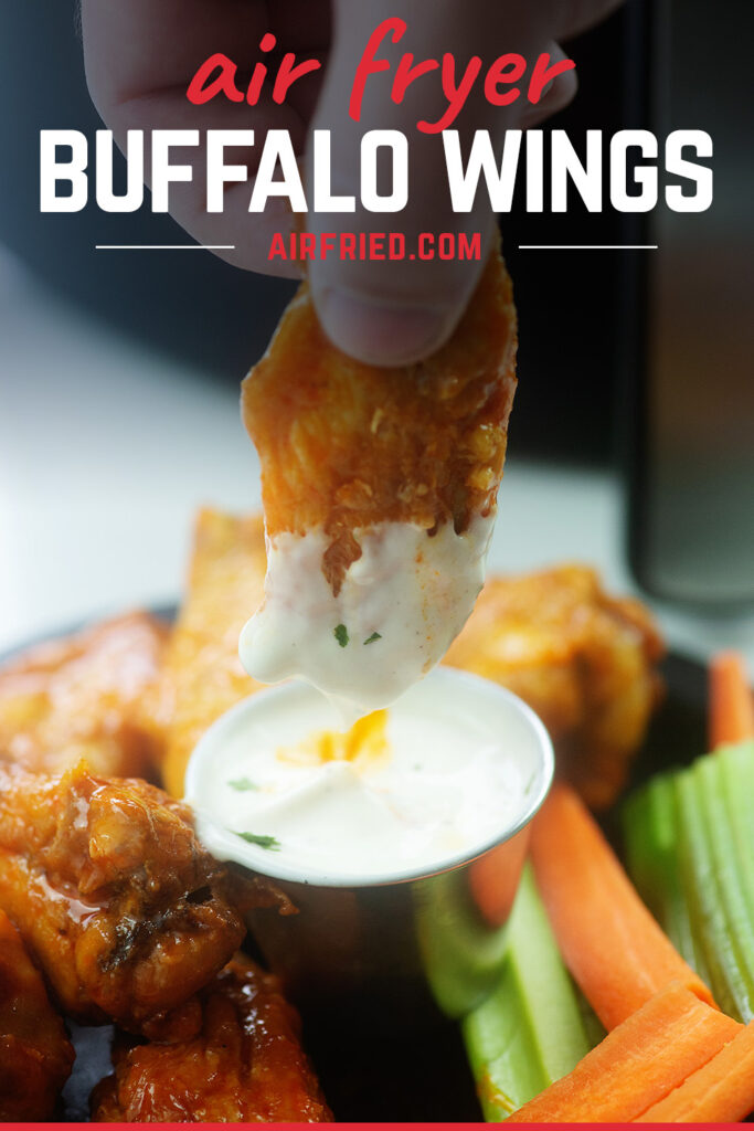 A chicken wing being dipped into ranch dressing
