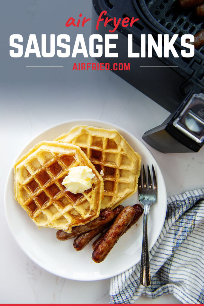 Overhead view of waffles and sausage links on a white plate.