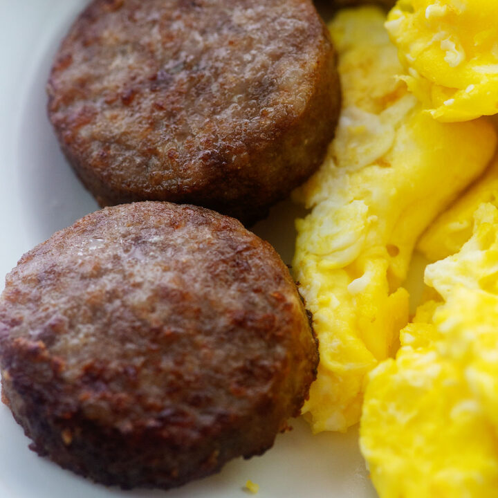 Close up of sausage patties on a white plate with scrambled eggs