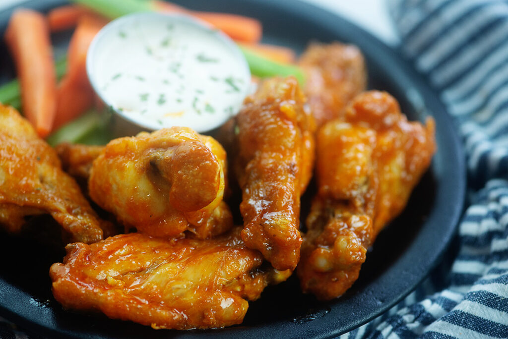 close up of chicken wings on a small black plate