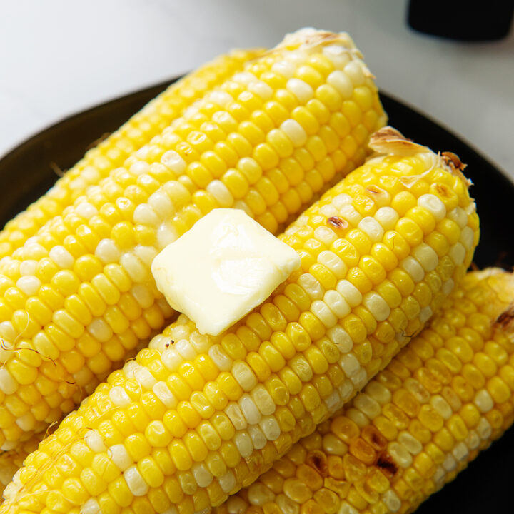 Butter on top of a pile of corn on the cob