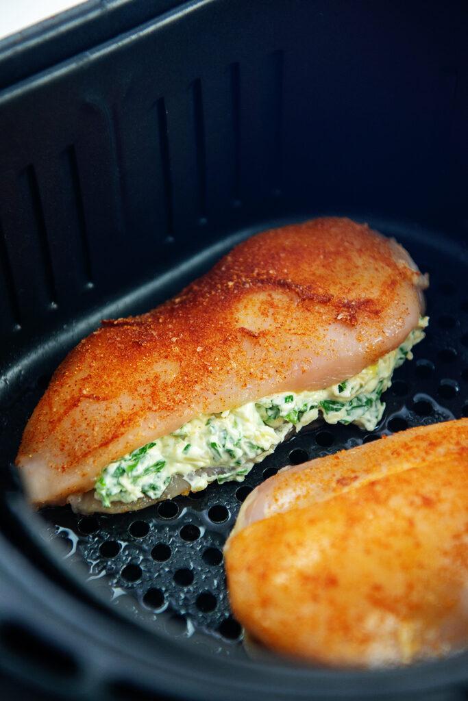 raw chicken breasts in an air fryer basket