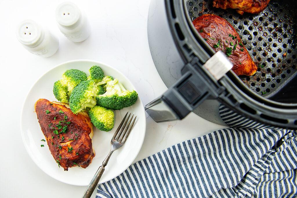 A plate of bbq chicken next to an air fryer