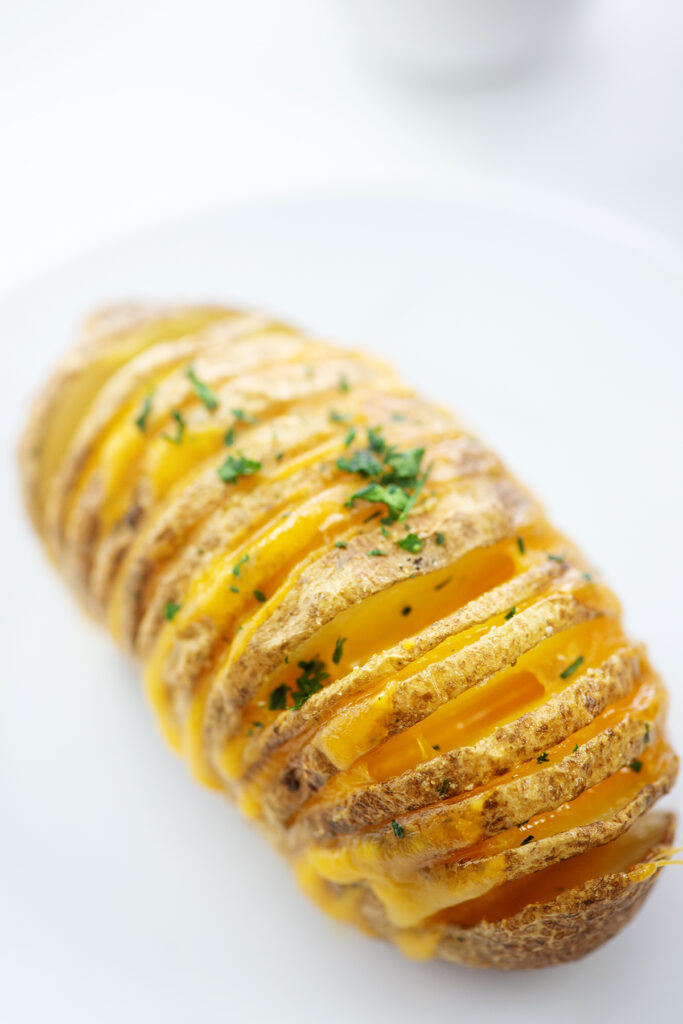 Hasselback potato with melted cheese with a white background