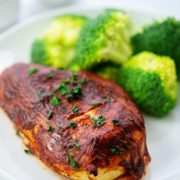 BBQ chicken and broccoli on a small white plate