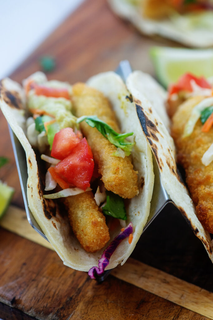 Close up of fish tacos in a taco tray on a wooden cutting board