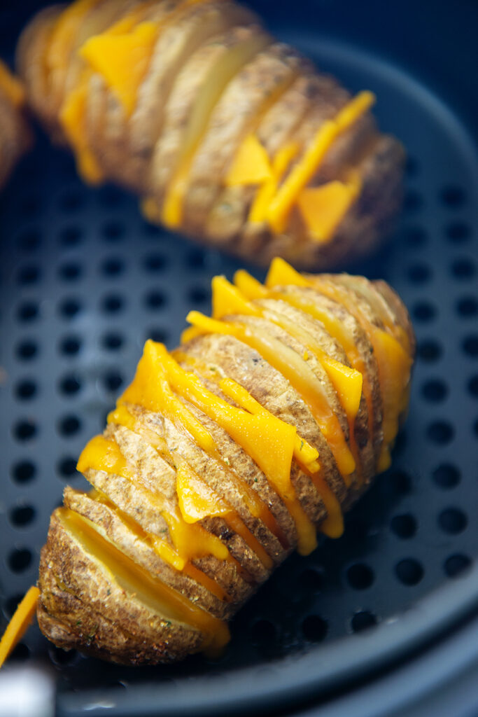 potatoes sliced with cheese in the slots made by the slicing in an air fryer basket
