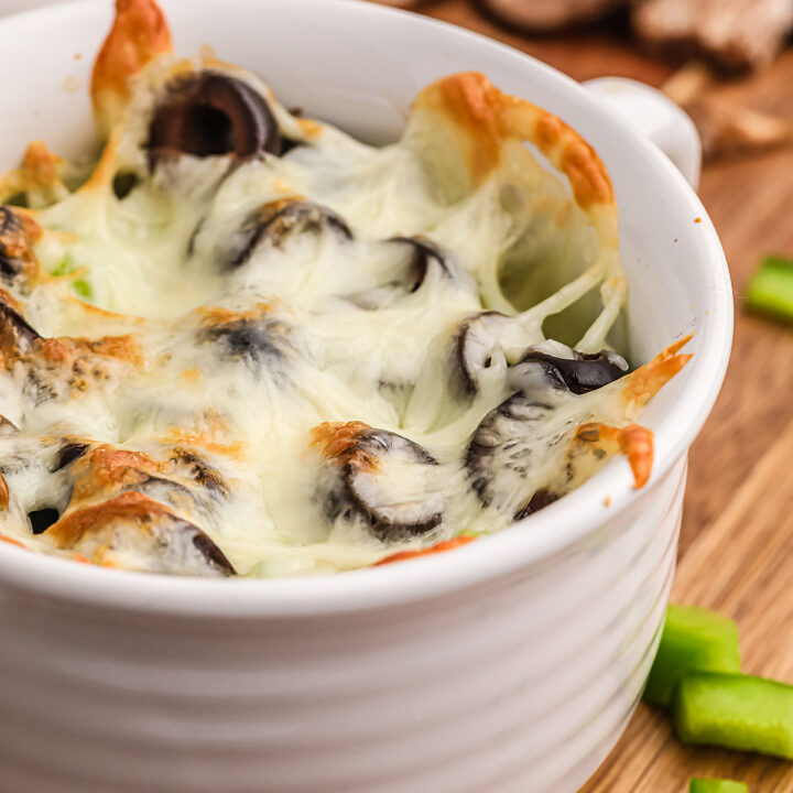 Close up of cooked pizza toppings in a ramekin