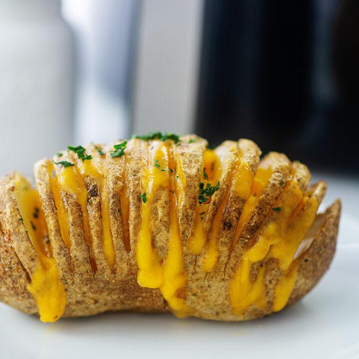 close up of a cheesy hasselback potato on a small white plate