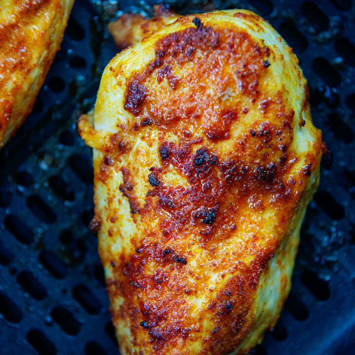 Close up of a chicken breast cooked in an air fryer basket