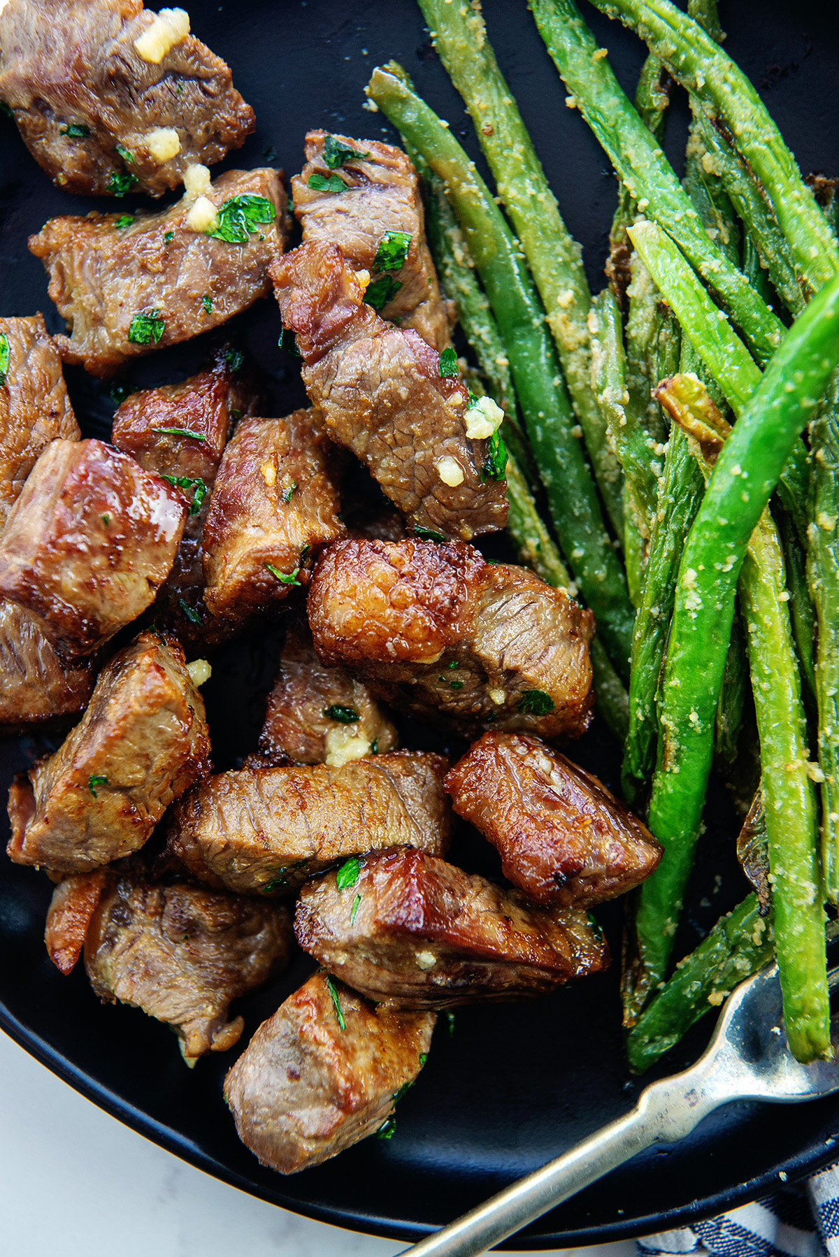Close up overhead view of cooked steak bites and asparagus on a black plate