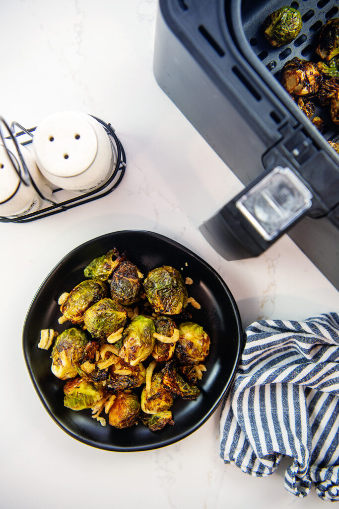 Overhead viiew of a plate of brussels sprouts in front of an air fryer