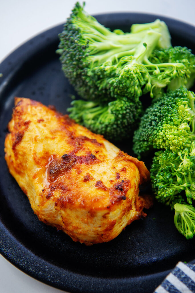 Close up of boneless chicken breast and broccoli on a plate