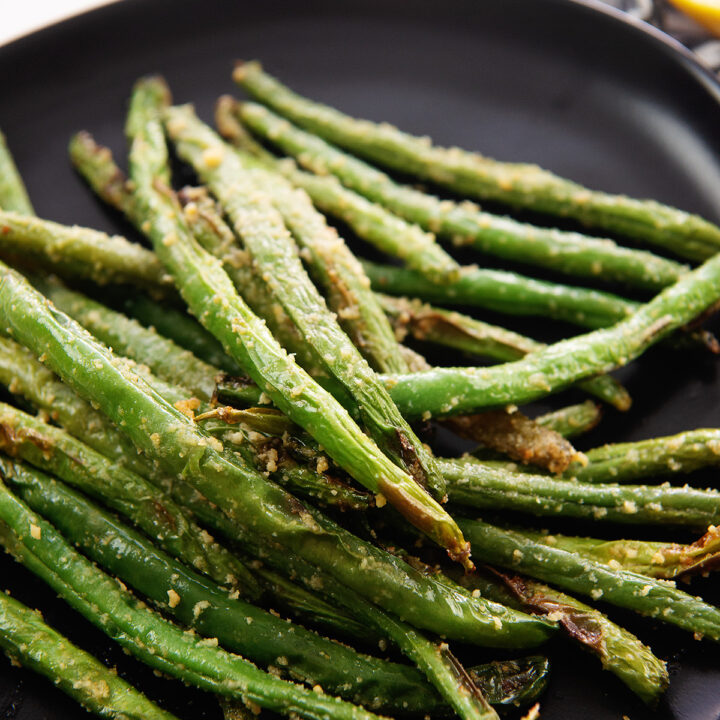Close up of roasted green beans on a small black plate