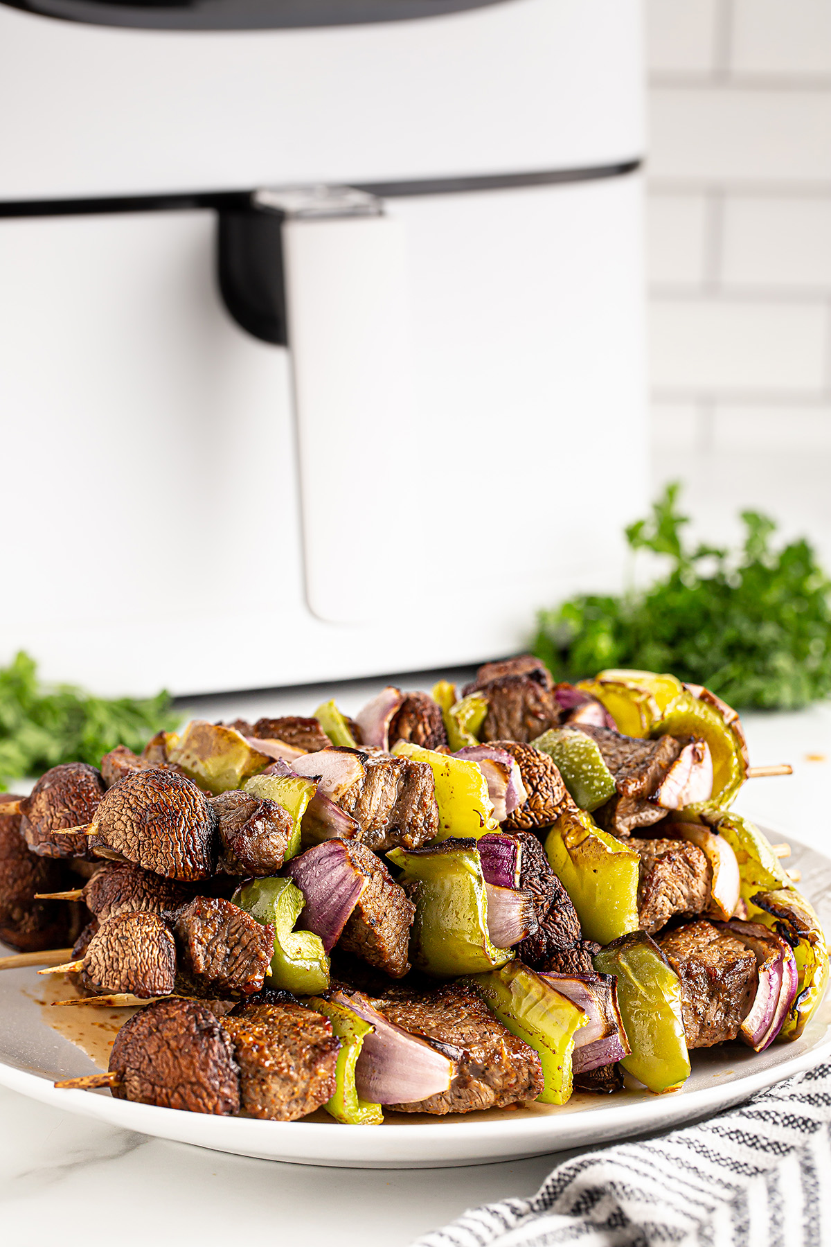 A plate full of kabobs in front of an air fryer