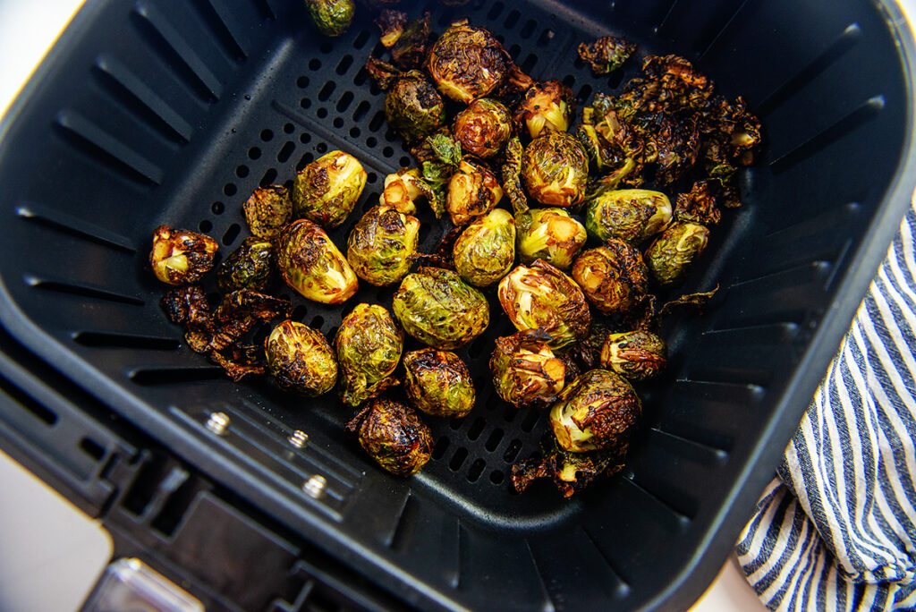 Overhead view of Asian brussels sprouts in an air fryer basket
