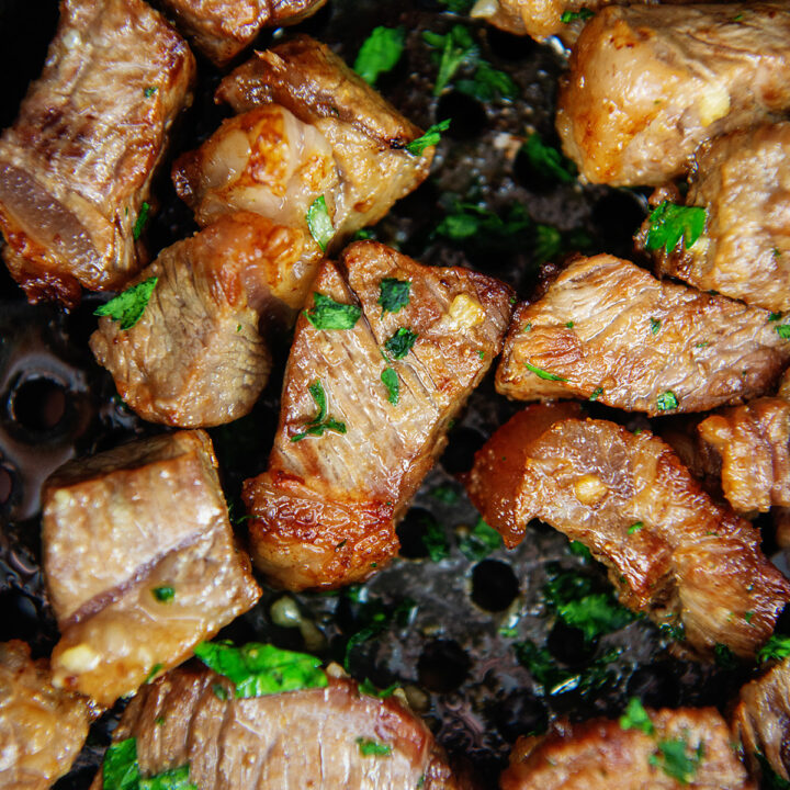 Close up of cooked steak in an air fryer basket