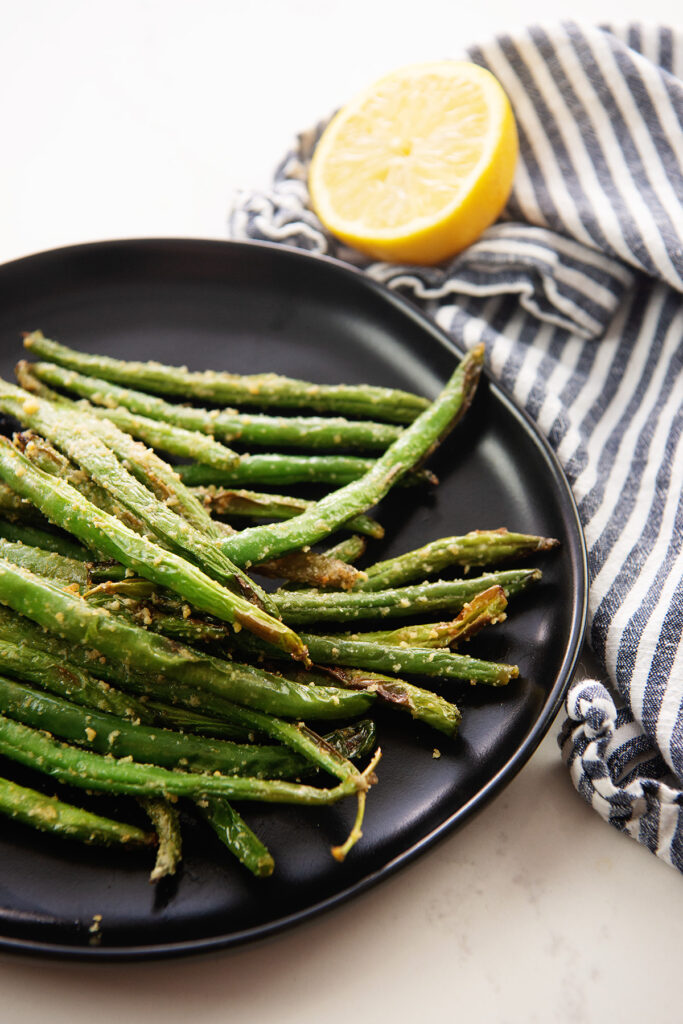 A plate of cooked green beans on a plate in front of half of a lemon