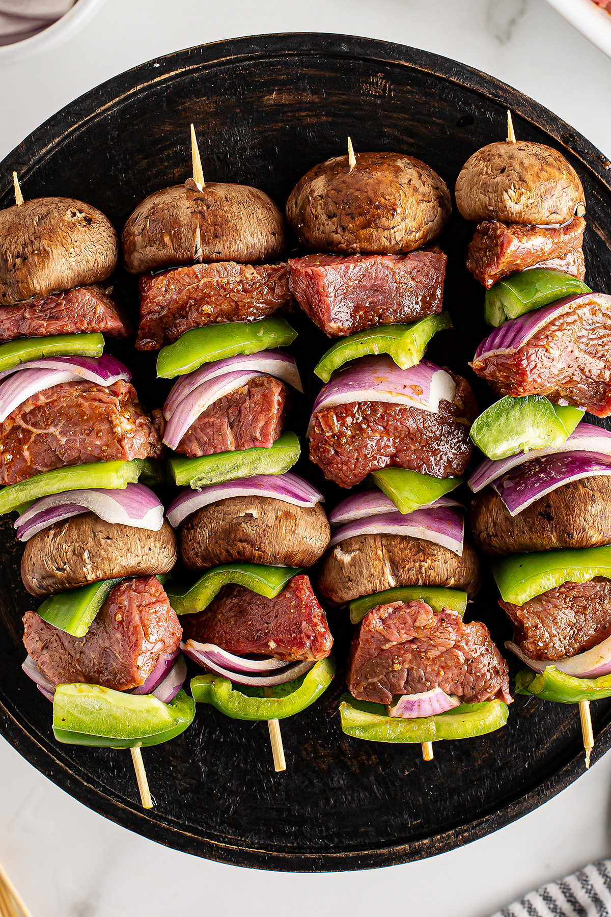 Overhead view of cooked steak kabobs on a black plate