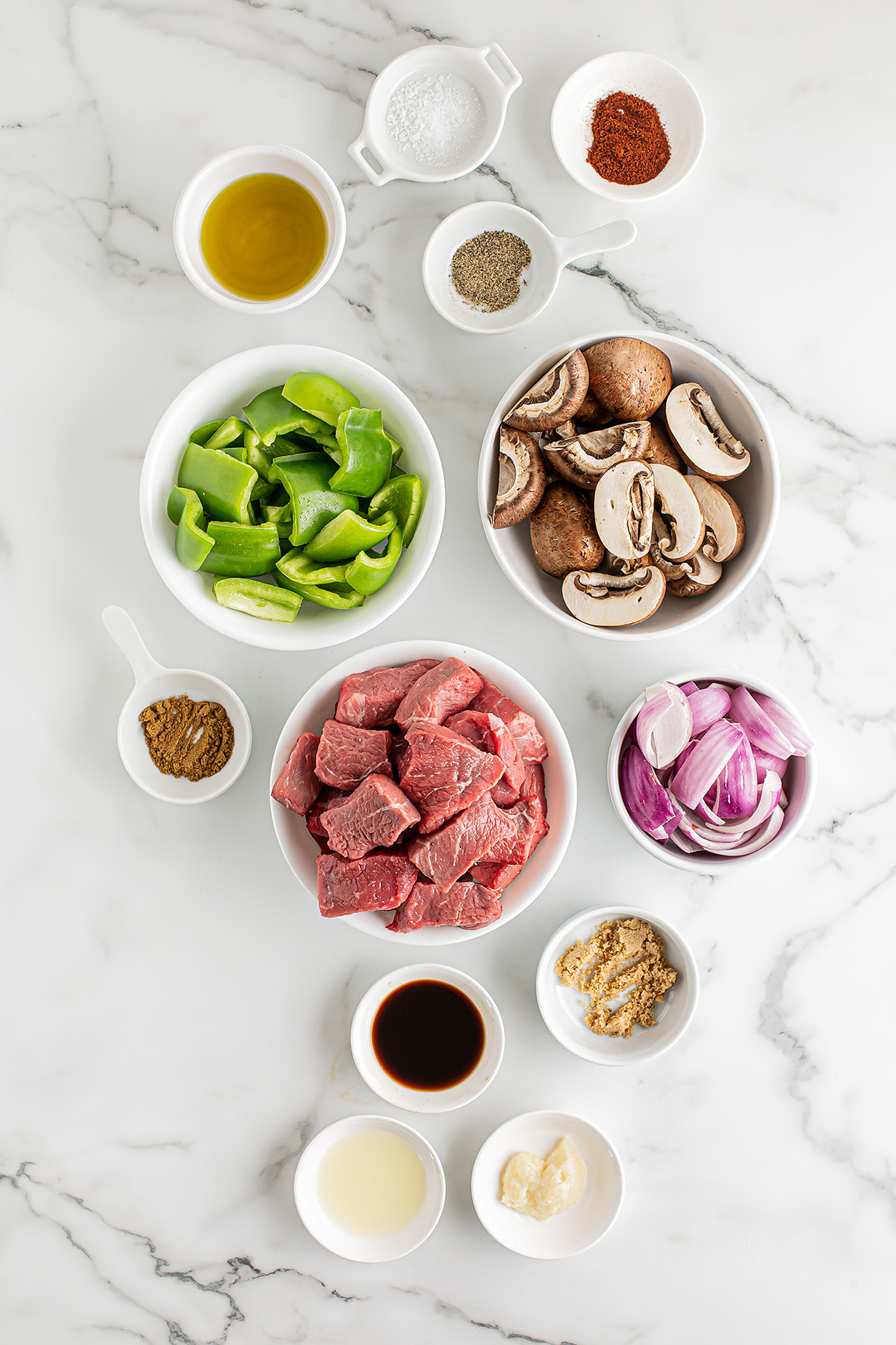 Raw ingredients for steak kabobs spread out on a counter
