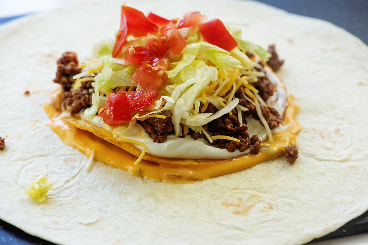Ingredients for crunchwrap supreme stacked up on top of each other on a tortilla