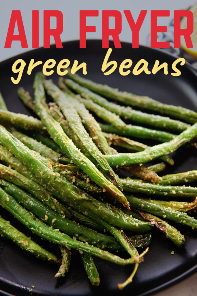 Close up of a pile of seasoned green beans on a black plate