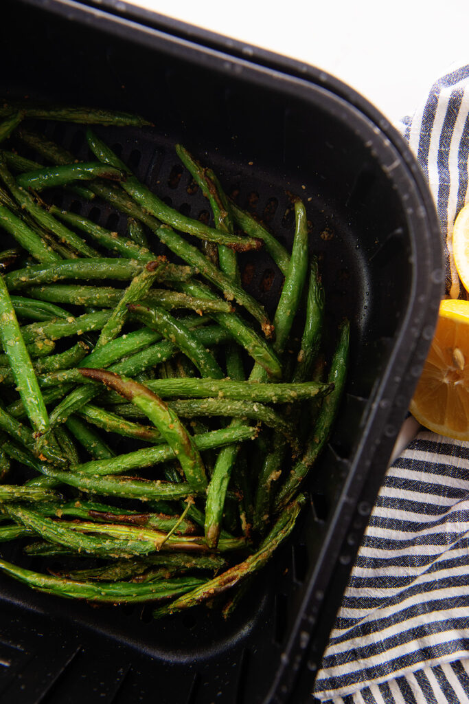 Overhead view of cooked green beans in an air fryer basket