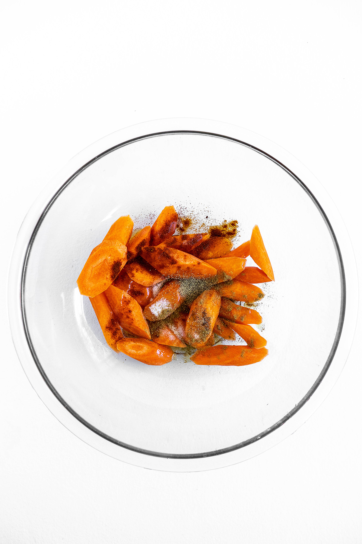carrots mixed with seasoning in glass mixing  bowl.