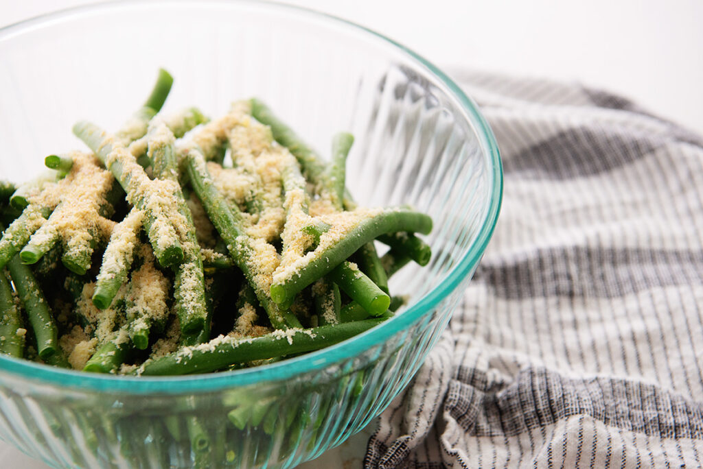 Close up of seasoning on top of raw green beans in a clear glass bowl