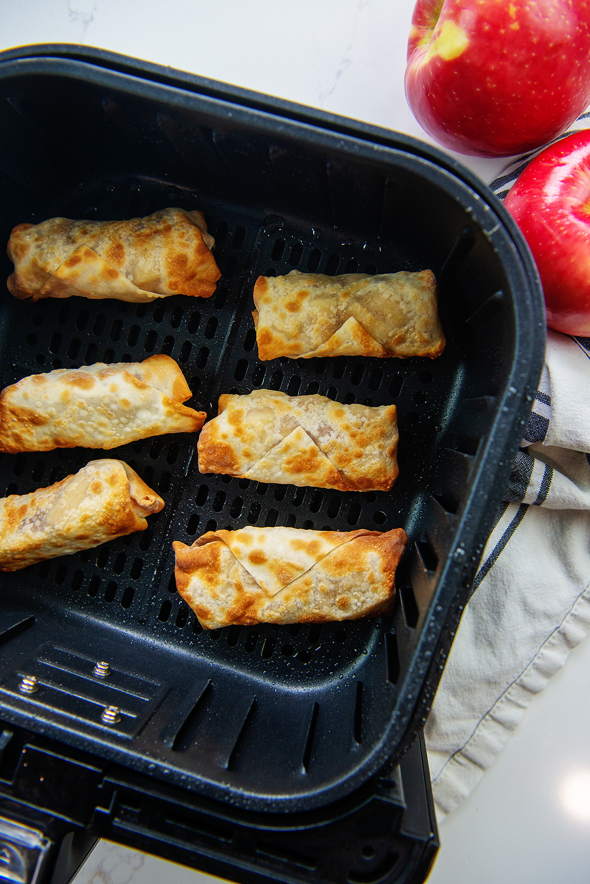 overrhehed view of six egg rolls in aan air fryer basket