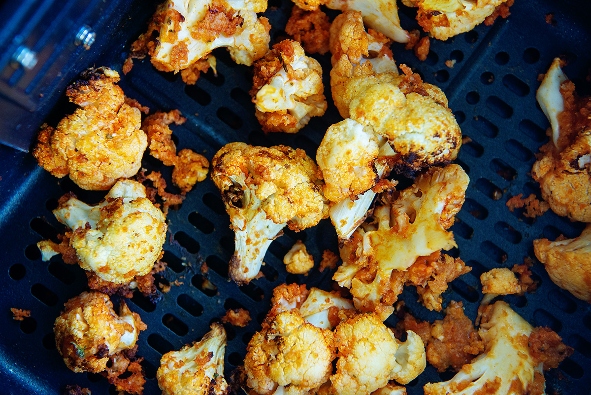 Cooked cauliflower spread out in an air fryer basket.